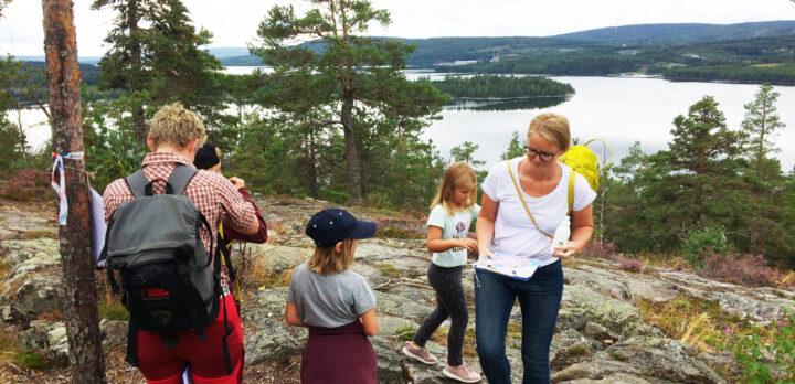 En familj står på ett berg med vacker utsikt över skog och hav, och ska börja gå en stig. Foto.