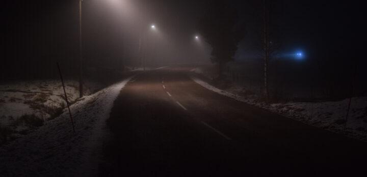 Landsväg en mörk natt, upplyst av gatlyktor. Långt bort kommer en bil. Foto.
