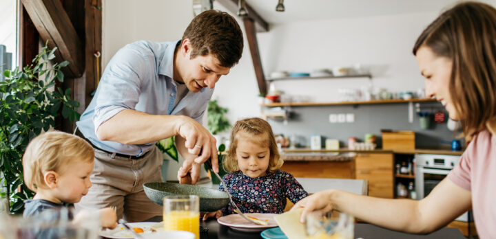 Father of a young family is putting eggs on a daughters plate for a breakfast. Foto.